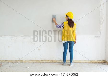 Female Worker Labor Plastering White Concrete Wall at Home House Construction Site as Interior Civil Renovation Work concept
