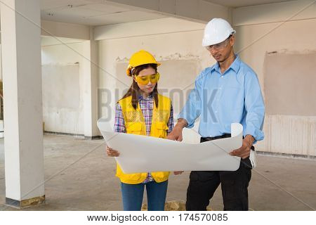 Architect and Constructor Discussion on Building Project Inspection with Architect plan at Construction site as Real Estate Development Concept.
