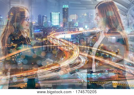 Double Exposure of Businesswomen handshake greeting and Expressway or Autobahn highway at Night as Business Partnership Teamwork concept