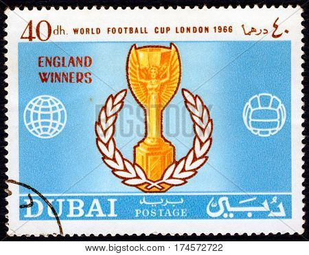 DUBAI - CIRCA 1966: Postage stamp printed in Dubai  with a picture of a football cup, with the inscription