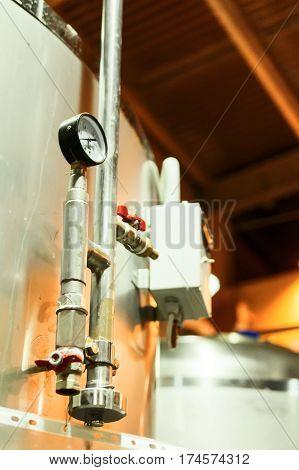 Modern Beer Factory. Metal tanks for storing beer. Temperature Gauge. Pipelines pressure control system in the tank.