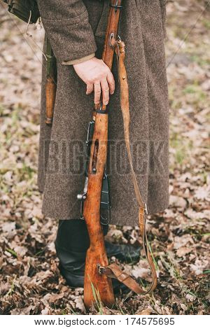 Re-enactor Dressed As Russian Soviet Infantry Soldier Of World War II Holds Rifle Weapon In Hands.
