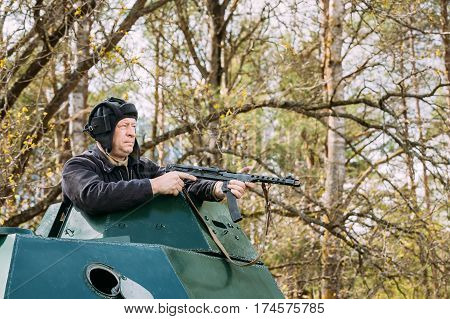 Pribor, Belarus - April 23, 2016: Re-enactor Dressed As Russian Soviet Crew Member Soldier Of World War II Sitting In Armoured Soviet Scout Car BA-64 In Forest And Aiming a Sub-machine Gun at Enemy