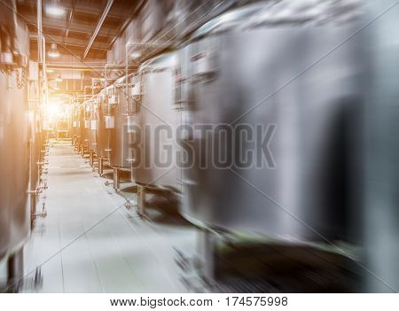 Modern Beer Factory. Rows of steel tanks for beer fermentation and maturation. Motion blur effect, sunlight