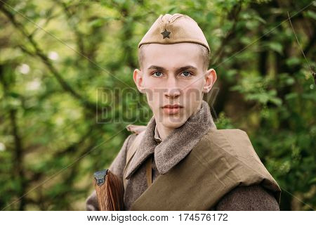 Pribor, Belarus - April 23, 2016: Close up portrait of Re-enactor Dressed As Russian Soviet Red Army Infantry Soldier Of World War II In Forest And Looking at Camera