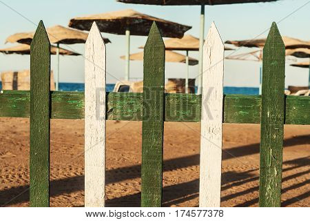 View Of The Beach With Thatched Umbrellas Through A Wooden Fence