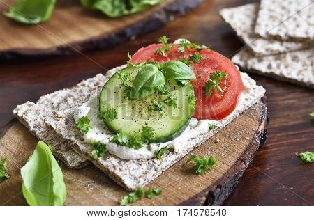 Healthy eating or dieting scene with crisp bread and fresh tomatoes and cucumber. Wooden table, rustic scene.