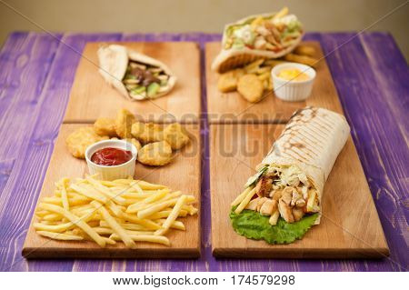french fries and nuggets Arabic shawarma Greek gyro and pita with chocolate and kiwi with two cups of cheese and ketchup on four wooden boards on a wooden purple table