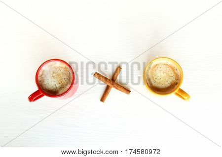 multiply sign of cinnamon sticks is between the colored cups of coffee with a frothy top view / double cappuccino