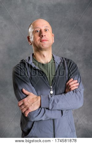Baldheaded Man With Crossed Arms In Front Of Gray Background