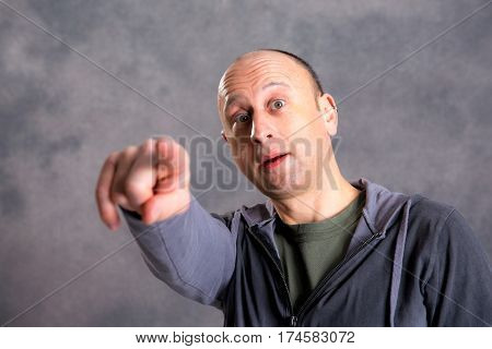 Baldheaded Man Pointing In To The Camera