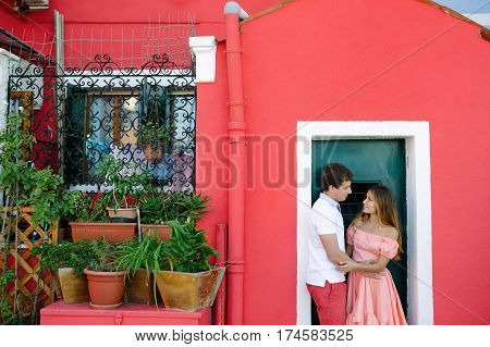 Tender couple in love near a typical Burano red house Venice Italy Europe