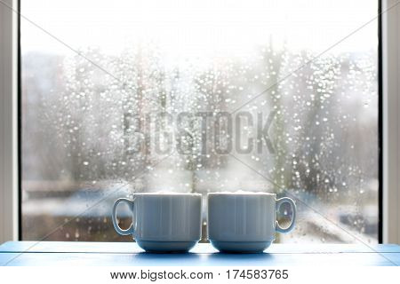 couple cup coffee with a frothy cappuccino in the background window with raindrops / cozy warming morning