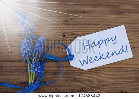 Label With English Text Happy Weekend. Sunny Blue Spring Grape Hyacinth With Ribbon. Aged, Rustic Wodden Background. Greeting Card For Spring Season