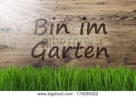 German Text Bin Im Garten Means I Am In The Garden. Spring Season Greeting Card. Sunny Aged Wooden Background With Gras.