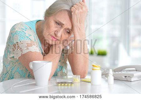 Portrait of a sick elderly woman with medication