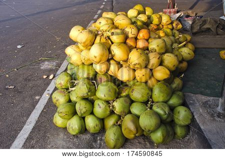 fresh raw coconuts fruits on street asphalt in South India