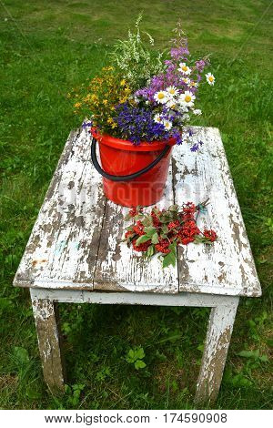 Various summertime wild flowers bouquet on old white wooden table in garden