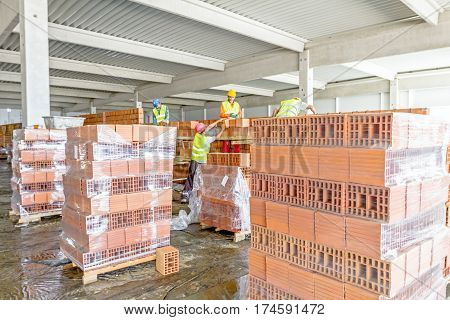 Masons bricklayer workers are building dividing indoor wall at the construction site.