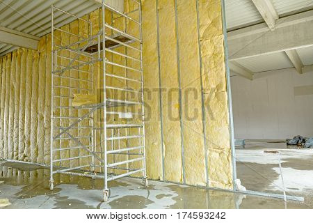 Mobile scaffold is used to complete dividing wall with thermal insulation mineral wool.