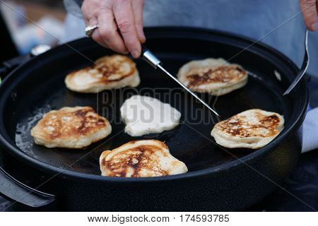 Photography of a cook during preparation of fritters