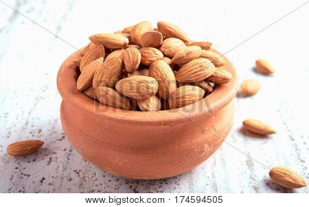 Almond on clay pot with wooden background