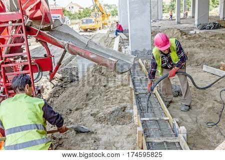 Zrenjanin Vojvodina Serbia - June 29 2015: Workers at building site are pouring concrete in mold from mixer truck.
