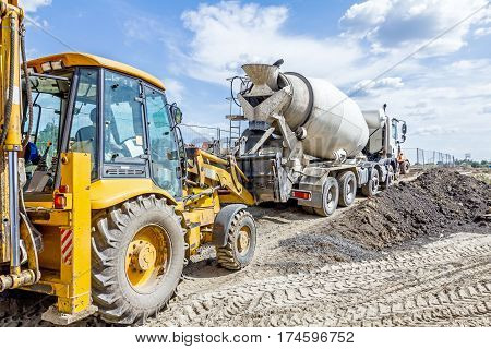 Concrete mixer truck is pouring fresh concrete into excavator bucket at construction site.
