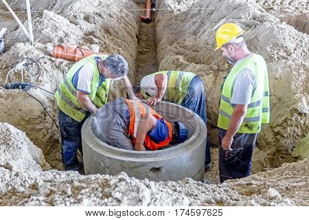 Zrenjanin Vojvodina Serbia - June 29 2015: Work is in progress. Construction workers are assembly new concrete manhole on building site.