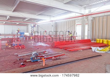 Workers are painting long round pipes in red using an airbrush gun at construction site.