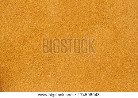 Texture of genuine leather close-up, cowhide. Soft sunny orange color. For natural, artisan backgrounds, substrate composition use, vintage design