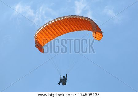 Paraglider using big ears to descend his wing