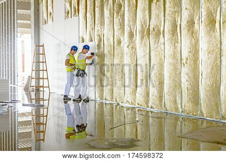 Zrenjanin Vojvodina Serbia - June 29 2015: Workers are assembly gypsum wall. Plasterboard is under construction using wooden ladder.