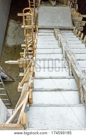 Concrete stairway is going down in a new unfinished building.