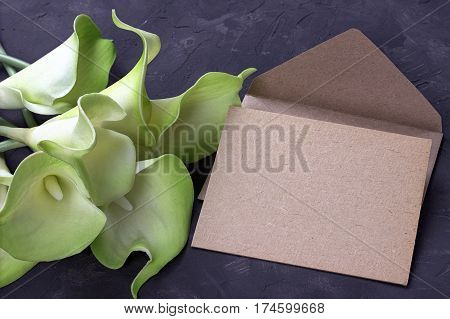 Green And Yellow Calla Lily Flowers With Envelope On Plaster Gray Background. Copy Space.