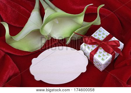 Green And Yellow Calla Lily Flowers Green Gift Box With Red Ribbon On Red Fabric Background Card For