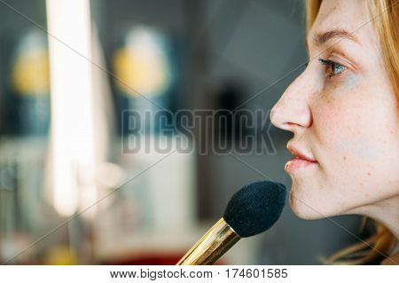 Beauty makeup artist woman by mirror in dressing room. Attractive female face Portrait. Professional stylist.