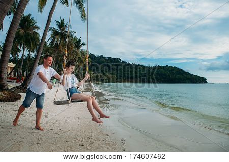Man ride his daughter on a swing tropical island phu quoc