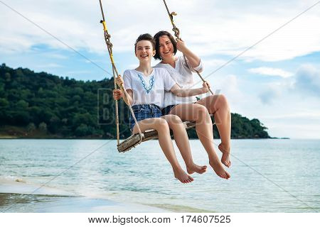 mother and daughter ride on a swing tropical island Phu Quoc