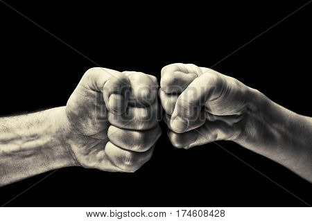 black and white image close up clash of two fists on black background. Concept of confrontation competition etc.