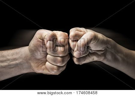 Image close up clash of two fists on black background. Concept of confrontation competition etc.