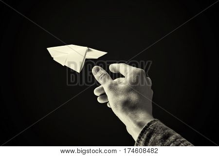 black and white image of a hand is throwing paper plane on black background.