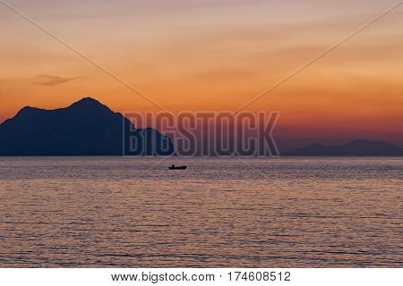 Small boat sunset silhouette is a fisherman's boat paddling along the water with a colorful purple and pink night sky in the background