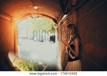 Adult blonde woman surfing internet via smart phone while standing in dark street tunnel and waiting her friend flirty lady is chatting with boyfriend using cell telephone on sunny summer day