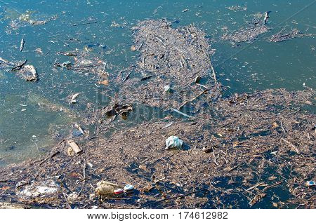 Waste trash and garbage floated on a polluted river