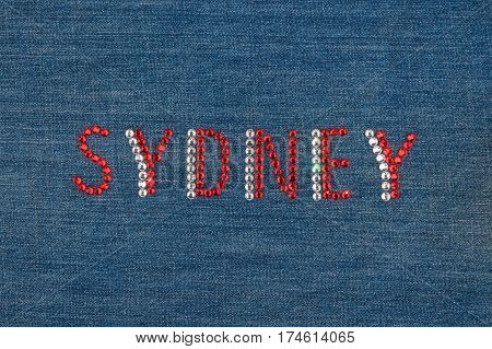 Inscription Sydney inlaid rhinestones on denim. View from above