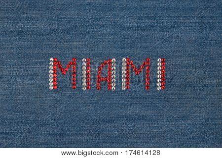 Inscription Miami inlaid rhinestones on denim. View from above