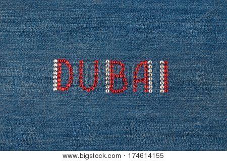 Inscription Dubai inlaid rhinestones on denim. View from above
