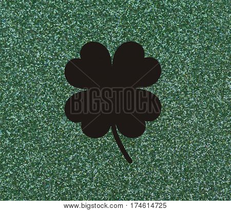 Clover with four leaves Black on a glittery green background.
