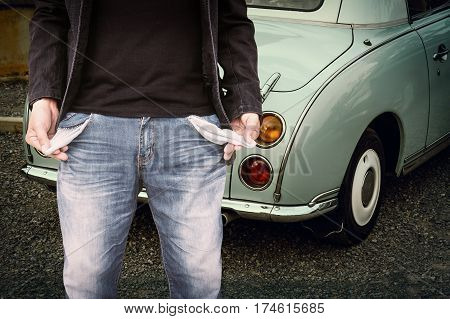 Man showing his empty pockets with classic car parked on the park.